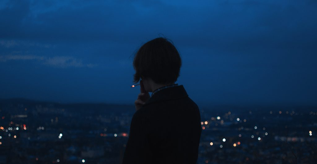 woman smoking facing a city