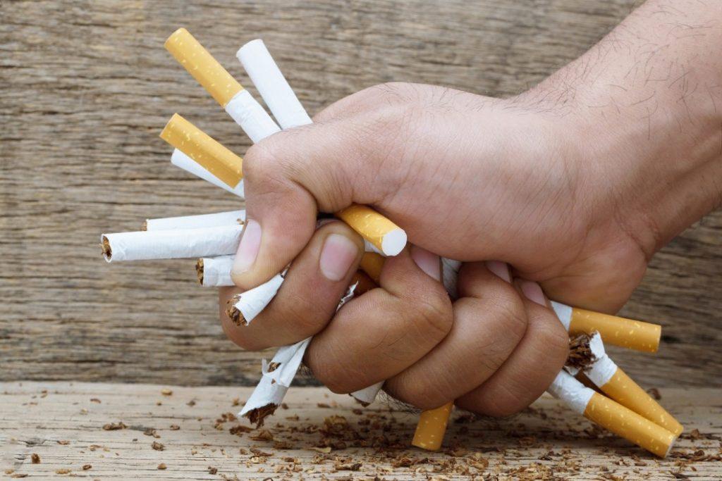 hand mashing cigarettes to quit